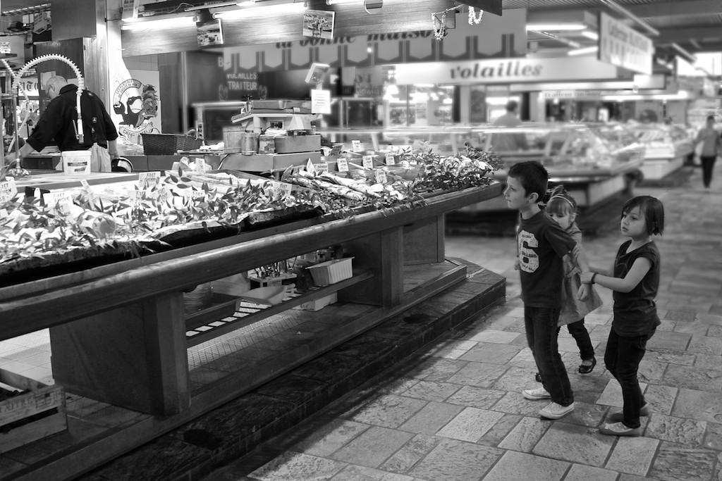 Un gruppo di bambini gioca intorno al banco del pesce, avvicinandosi quando il proprietario è di spalle e scappando via quando si gira. ©Francesca Semisa